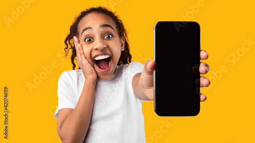 Excited black girl showing blank empty smartphone screen for mockup