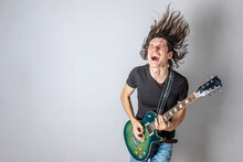 Young Man Is Playing An Electric Guitar Singing And Waving His Long Hair. Emotional Performance Of Rock And Roll