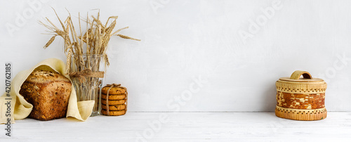 Fotografia, Obraz banner with a white wall background and copy space - Homemade grain bread and a linen napkin