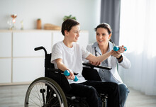 Physical Rehabilitation Concept. Young Physiotherapist Helping Teenage Boy In Wheelchair To Do Exercises At Home
