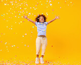 Excited African American kid jumping and catching confetti on birthday in studio