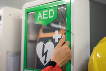 Action Of A Medic Rescue Staff Is Opening AED Station Box To Take The AED Machine, Using To Help A Heart Attack Patients. Health Care And Medical Action Photo. Selective Focus On People's Hand.