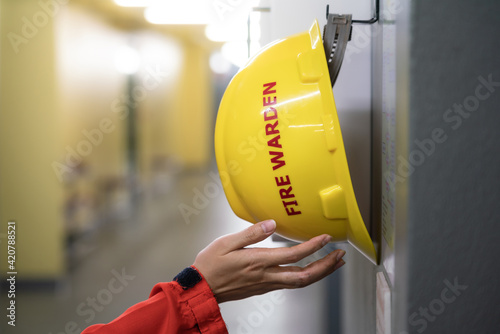 Canvas Print Action of fire fighter is taking a Fire Warden safety yellow hardhat helmet that hang on the wall, Response for emergency situation