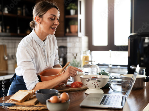 Fototapeta Young woman cooking in the kitchen. Beautiful woman following recipe on laptop and preparing delicious food. obraz