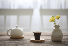 Small Tea Cup And Teapot With Flower Vase On Wooden Table