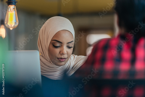 Obraz na plátně African muslim girl wearing hijab working on a laptop in a modern startup company