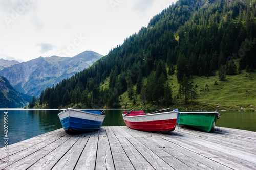 Fotografie, Obraz Three rowing boats laying on a wooden landing stage at an idyllic mountain lake in the alps