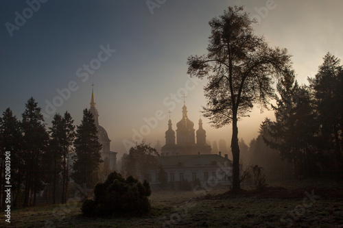 Tableau sur Toile Orthodox church in the morning fog at dawn in the middle of the park