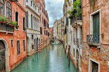 Canal With Boats In Venice (Italy) On A Cloudy Day In Late Autumn