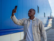 Handsome black Spanish male taking a selfie with his smartphone