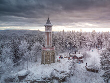 Aerial Photo Of Lookout Tower Stepanka On The Border Of Krkonose And Jizera Mountains. Winter Overcast Day, Sky With Clouds, Trees Covered With Snow.