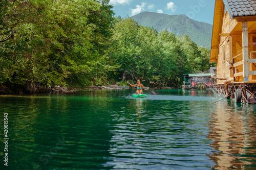 Female on stand up paddle board on beautiful lake Fototapete