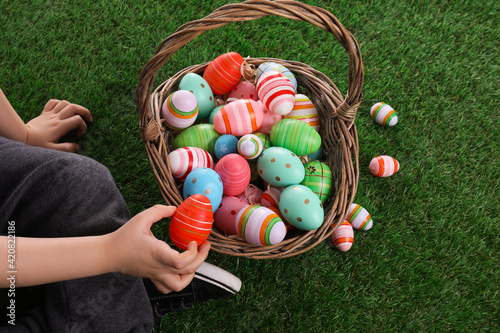 Little boy with basket full of dyed Easter eggs on green grass, closeup Fototapet