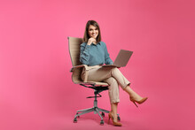 Young Businesswoman With Laptop Sitting In Comfortable Office Chair On Pink Background