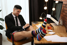 Businessman In Jacket And Underwear Having Videocall On Computer At Home Office