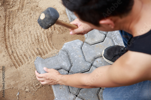 Fotografie, Obraz Hand of professional paver worker lays paving stones in layers for pathway