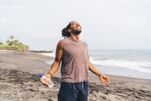 Happy Black Man Enjoying Summer Day On Beach After Workout