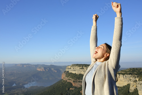 Fototapeta Excited casual woman celebrating vacation in the mountain