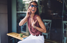 Cheerful Emotional Female In Sunglasses Talking On Mobile Phone Via Roaming Connection Sitting Outdoors, Happy Beautiful Woman Surprised With Receiving Call Having Positive Smartphone Conversation