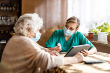 Home Caregiver Helping Senior Woman With Medication