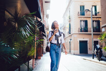 Happy Caucasian Woman In Trendy Wear Walking On City Street During Vacation Holiday In Morning, Smiling Female Traveler Strolling On Downtown Explore Destinations Holding Disposable Cup