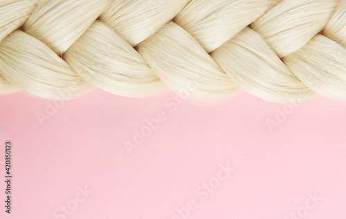 Obraz Smooth white beautiful pigtail. The braid is braided by a blonde on a pink background. The concept of hairdressing, hair purchase, hair health, hair extensions. Top view. Flatlay.Copyspace. - fototapety do salonu