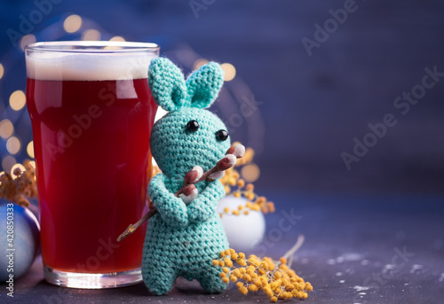 Fototapeta A glass of beer on the table with Easter eggs, a copy space card. Easter knitted rabbit, soft toy obraz na płótnie