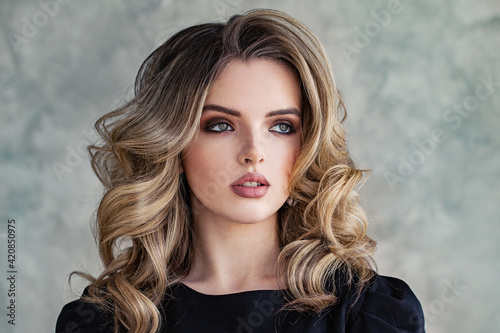 Fototapeta Lovely woman model with curly hairstyle on gray background portrait obraz