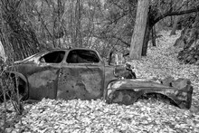 Black And White Photograph Of Abandoned, Old, Rusted, Bullet Ridden Car On Trail In A California Valley.