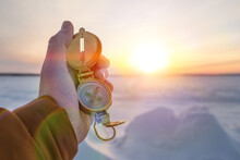 Old Compass In Hand Against The Background Of The Winter Sunset. Tourism, Travel. Navigation Orienteering Gps