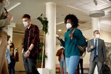 Black Female Student Wearing Face Mask While Walking Through University Hallway.