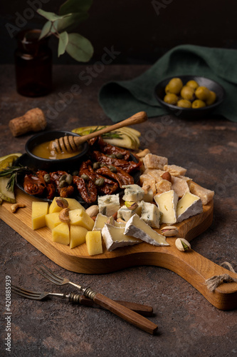 Valokuvatapetti Cheese platter with different cheeses, dried tomatoes, nuts, honey and dates on rustic wooden background