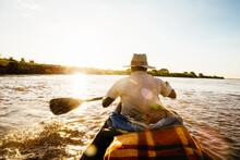 Rear View Of Man Rowing Boat OnTsiribihina River, Madagascar, Africa