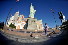 Mid Adult Female Runner Running In Front Of Statue Of Liberty On Las Vegas Strip, Las Vegas, Nevada, USA