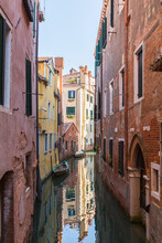 Narrow Canal With Moored Boats, Old Architectural Style Stucco And Brick Residential Buildings, San Marco, Venice, Veneto, Italy