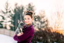 Girl Hugging French Bulldog Puppy Outdoors