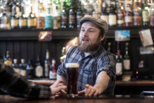 Barman Serving Beer To Customer At Bar In Traditional Irish Public House