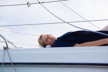 Mature Woman Sunbathing On Sailboat On Chiemsee Lake, Portrait, Bavaria, Germany