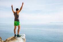 Runner Raising Arms In Victory On Protruding Rock, Santa Barbara, California, USA