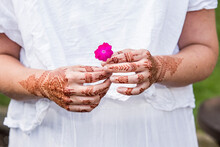 Woman In White Dress With Henna Tattoo On Hands Holding Flower