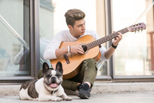 Teenage Refugee Boy Playing Guitar On Pavement With Dog
