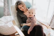 Baby Boy Sitting On Mother's Lap, Portrait