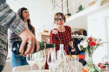 Friends Celebrating With Champagne In Loft Office