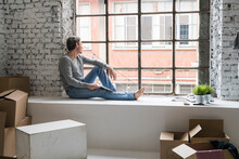 Man Moving Into Industrial Style Apartment, Sitting On Window Ledge Looking Through Window