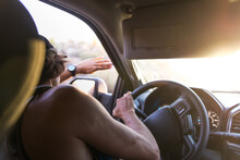 Man Driving Car Shielding Eyes From Sunlight, Over Shoulder View