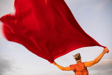 Woman Holding Up Red Cloth Fluttering In Wind