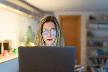 Female Higher Education Student Looking At Laptop In University Study Area