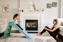 Girl Sliding Down Living Room Slide, Mother Watching