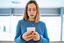 Female Higher Education Student In University Looking At Smartphone