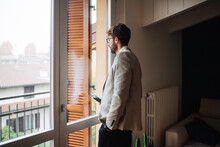 Mid Adult Man Holding Smartphone Gazing Out Through Apartment Window